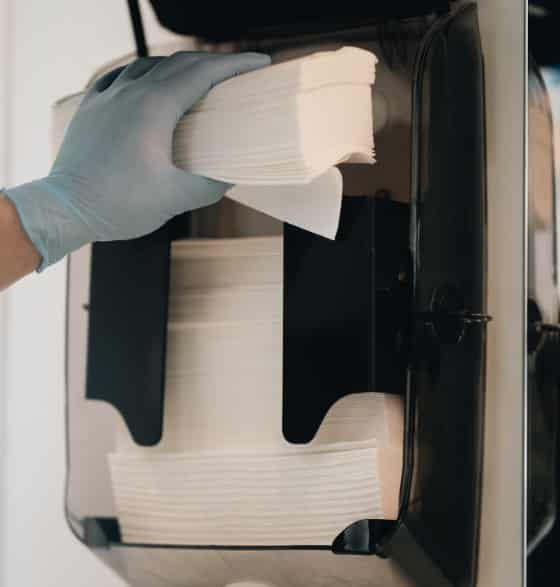Close up picture of a hand placing paper in a dispenser.