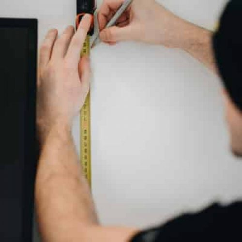 Picture of a DUUO handyman who is measuring something on the wall.