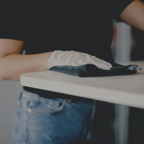 Picture of a DUUO employee's hand. The person is wiping a table surface with a cloth.